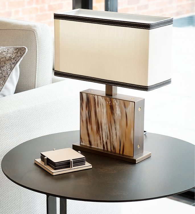 a small side table with a freestanding lamp made with natural horn materials