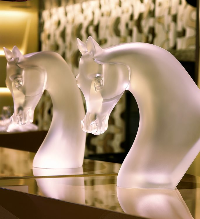 two crystal horses heads on a bar top
