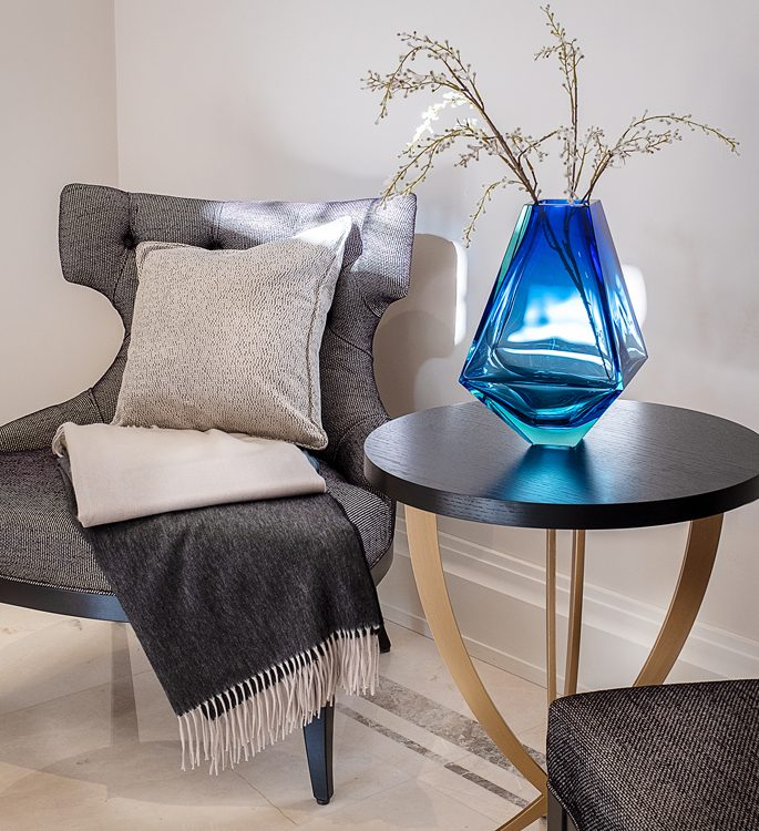 a chair with a luxury cashmere throw and a crystal vase