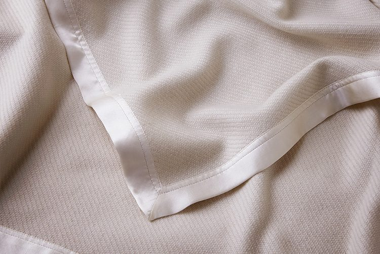 a cream cashmere throw with silk borders and a patterned weave