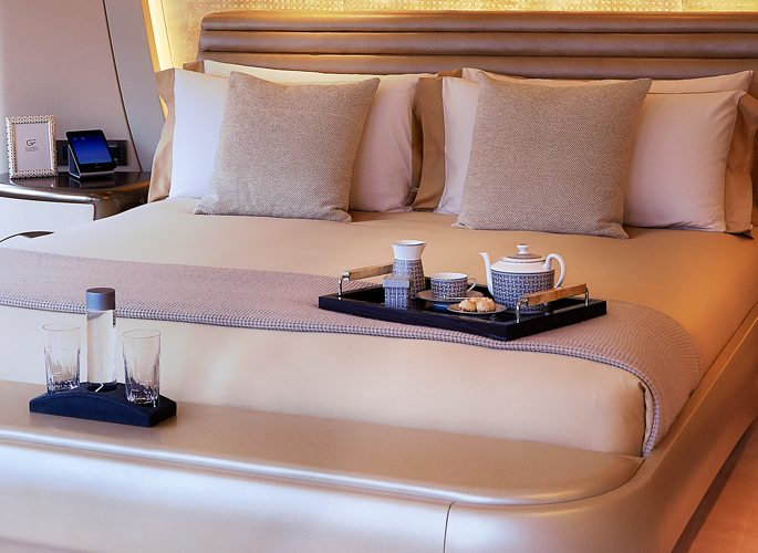 pink bed linen, a tea set and water jug on an emperor bed