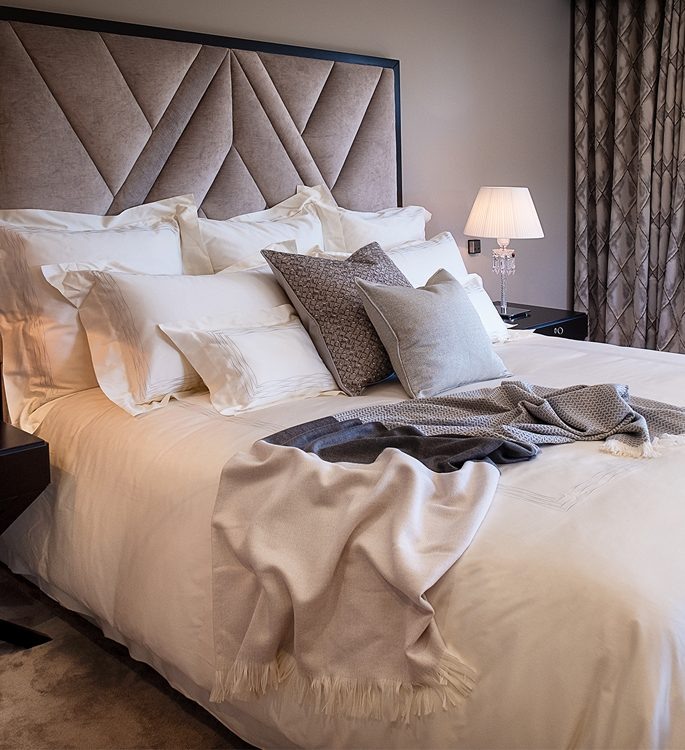 a king size bed with irory bed linen, grey cushions and a ombre blue cashmere throw