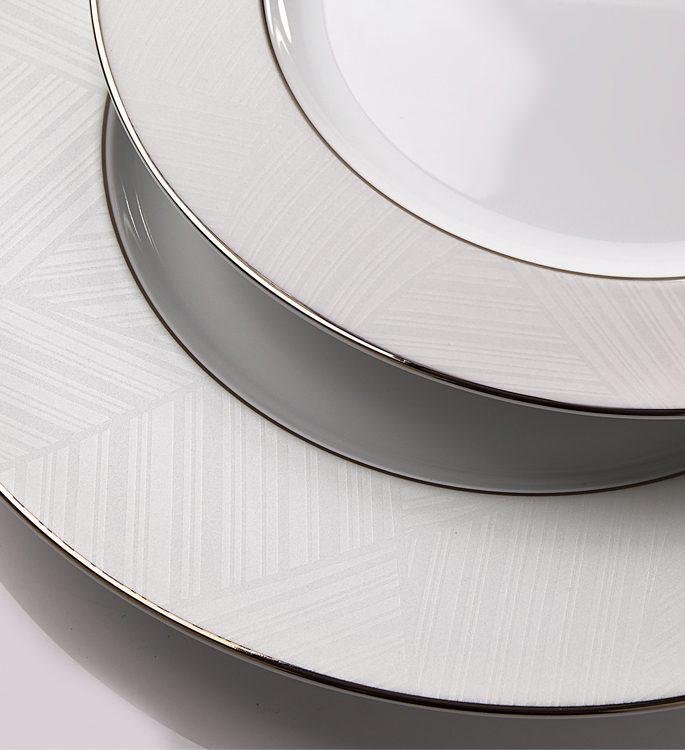 a close up of two porcelain plates with ice white line decorative details