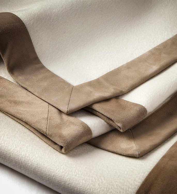 a cream cashmere throw with brown suede borders