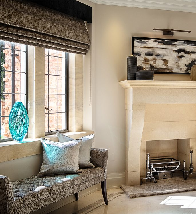 a fireplace with a long chair and lots of silver cushions