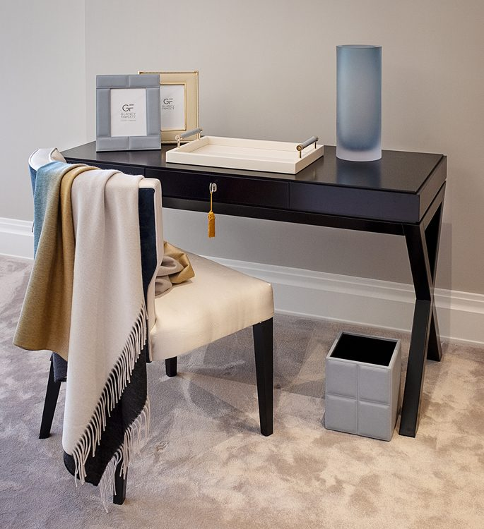 dressing table with photo frames, a trinket tray, vase and a cashmere throw hanging from the chair