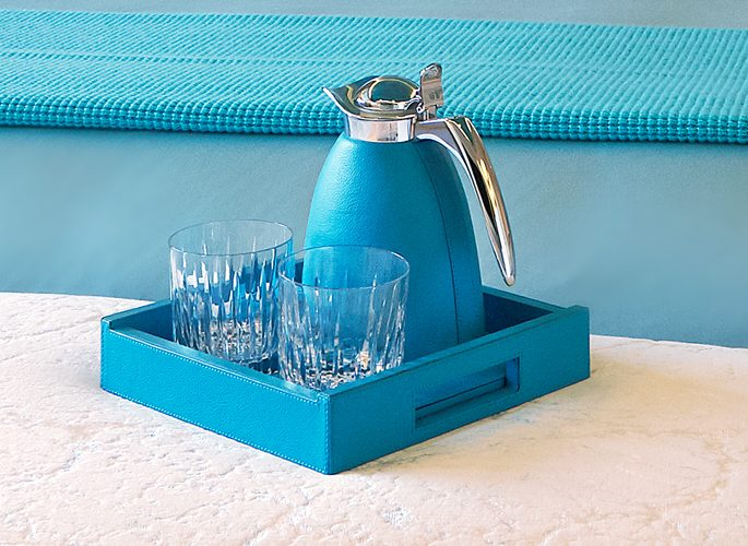 a water jug and glass set in bright blue made from leather