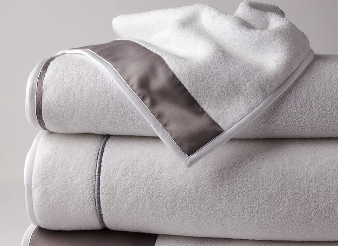 a stack of folded towels with grey shimmery embroidery