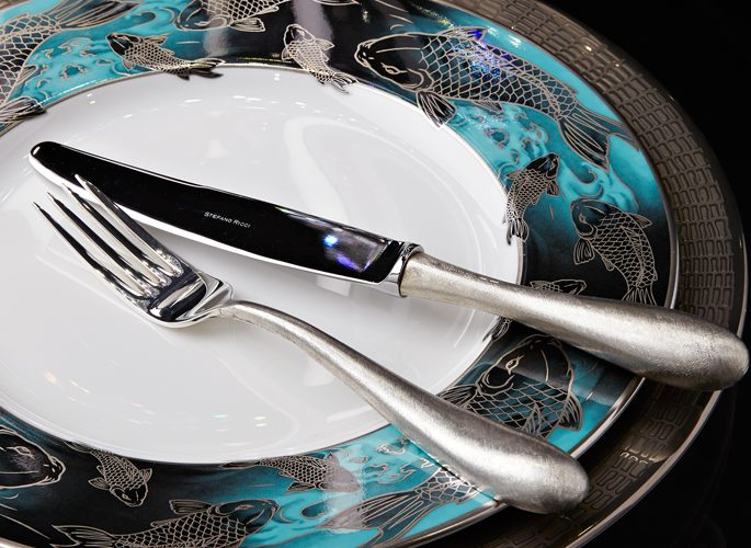 blue and silver koi carp fish patterned porcelain plate with table linen and cutlery