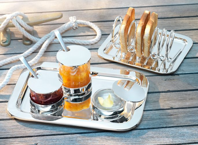a sterling silver toast rack with a silver tray containing jams and spoons