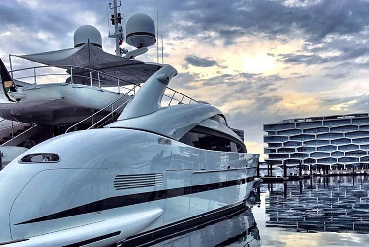 a superyacht in a marina in the evening as the sun sets