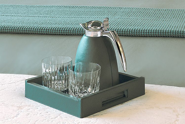 a leather skinned water jug and glass set in a striking teal colour