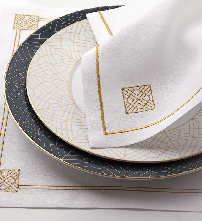 white and gold art deco patterned porcelain plate with table linen and cutlery