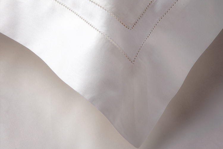 the corner of a pillow case with white bed linen