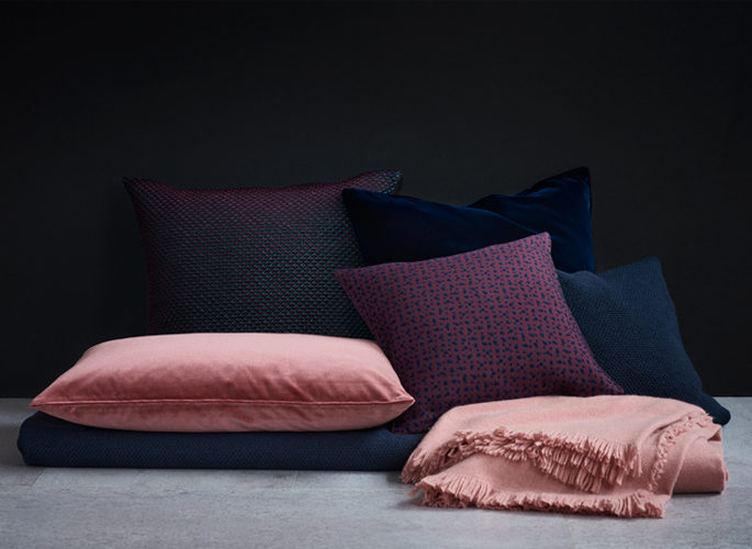 a pile of dark blue and light pink cushions lying on a dark blue cashmere throw