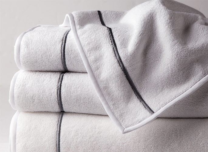 a stack of white towels with a single silver embroidered line