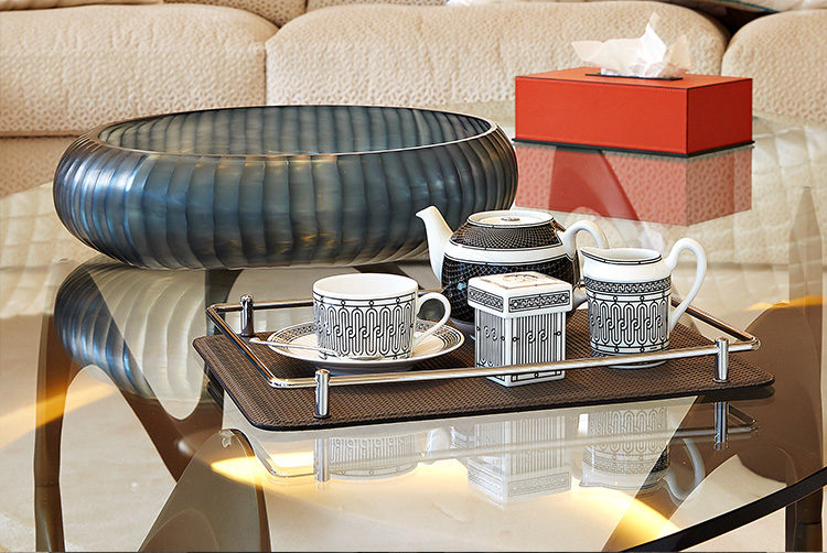 a table with a black and white hermes tea set with a red tissue box