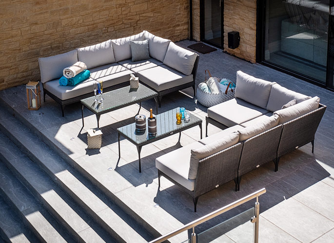 a sunny deck area with champagne and crystal glasses