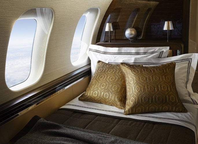 private jet bedroom with luxury gold bed linen and a view of clouds out the window