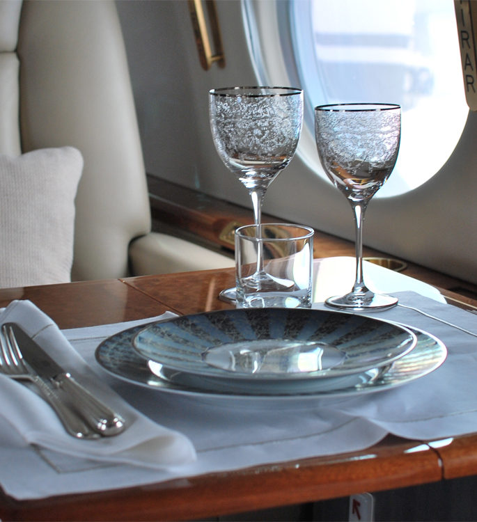 a private aircraft dining table by the window with luxury tableware