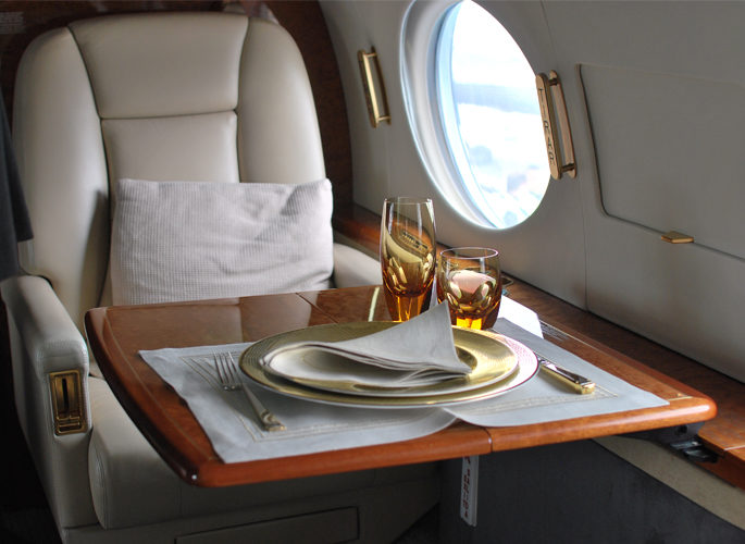 a private aircraft dining table by the window with luxury tableware and amber crystal