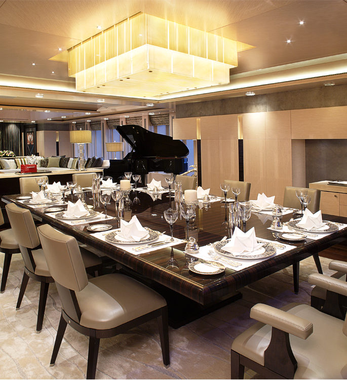 a vast dining room with a large table, luxury tableware and a grand piano