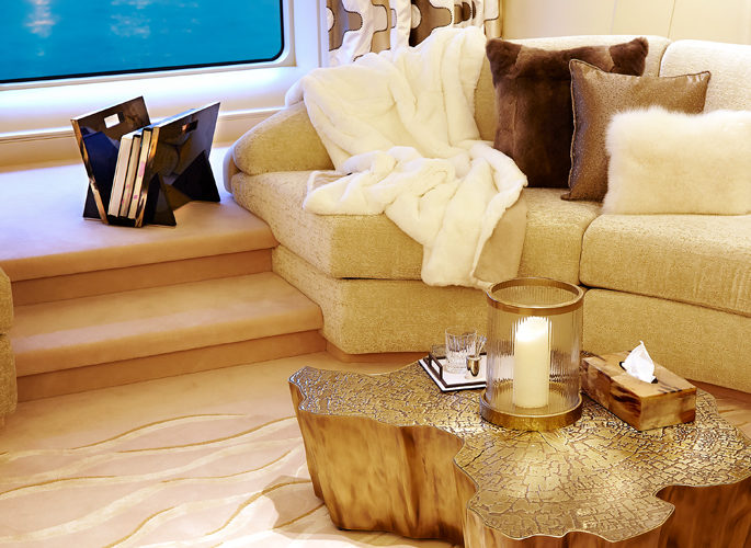 sitting room of motor yacht Aviva; a sofa with a luxury throw and accessories