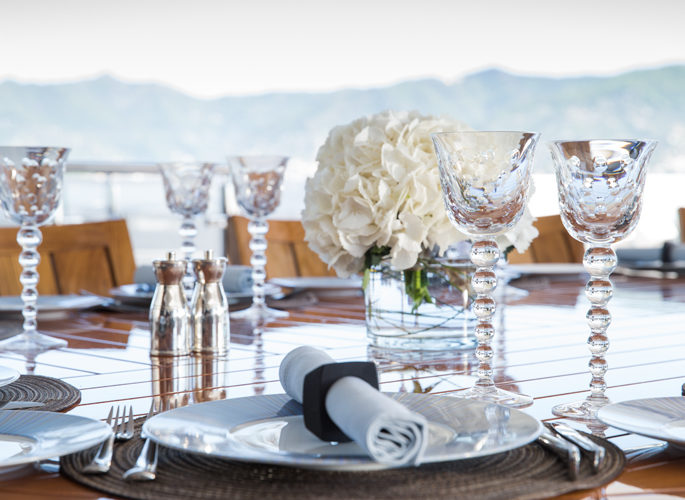 macro view of motor yacht Turquoise's outside dining table laid for entertaining
