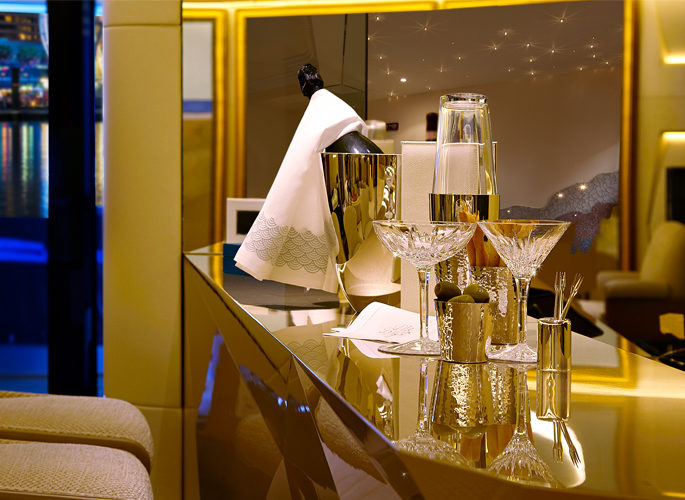 a superyacht bar set with a champagne bucket and crystal martini glasses