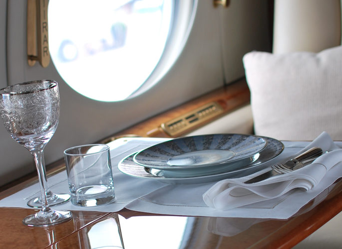 a private jet window with a dining setting of luxury tableware