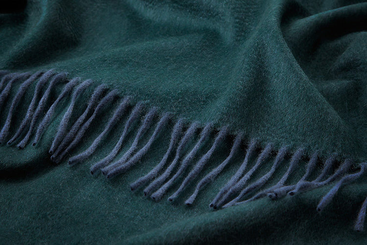a dark green cashmere throw with darker blue tassles