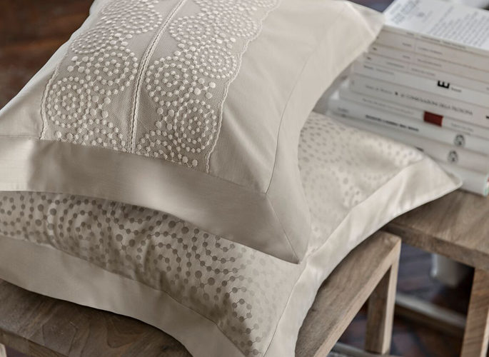two ivory pillows with beaded style embroidery and silk oxford borders