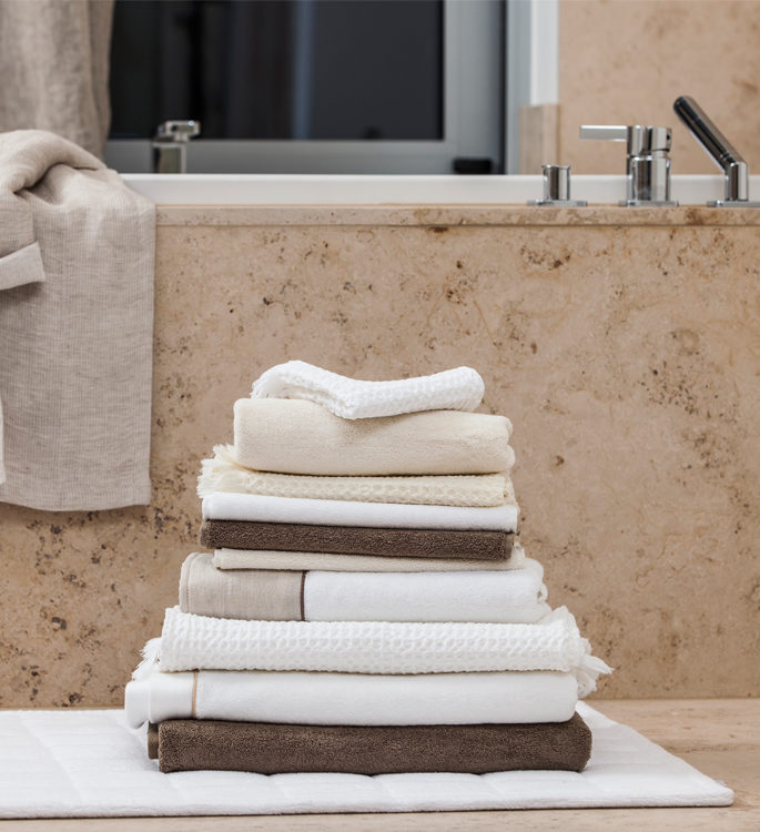 a stack of neutral coloured towels next to a bath on a bathmat