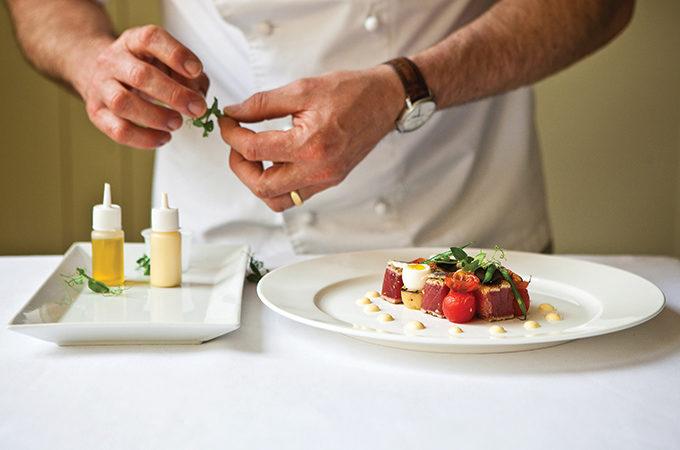 a man cooking and preparing gourmet food
