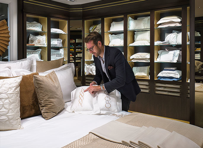 Project Manager showcasing the embroidered detailing on a cushion to a client in the Glancy Fawcett Linen Showroom