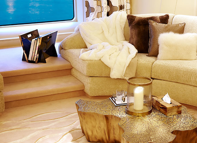 Superyacht living space with luxury cushions, fur throw over a sofa and accessories for the table