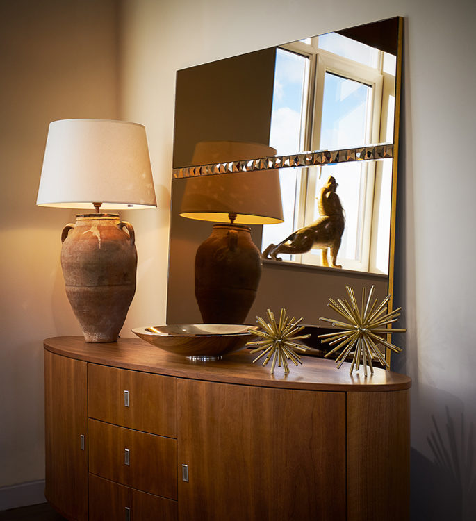 a swarovski crystal mirror behind a table with a lamp and decorative accessories
