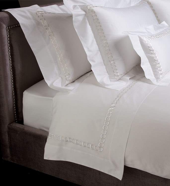 white bed linen with silver embroidery and an oxford border