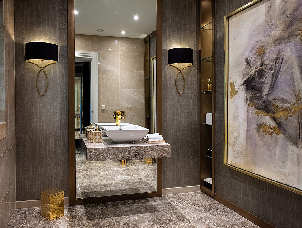 a luxury bathroom with marble floors and gold metallic detail on the furnishings and accessories