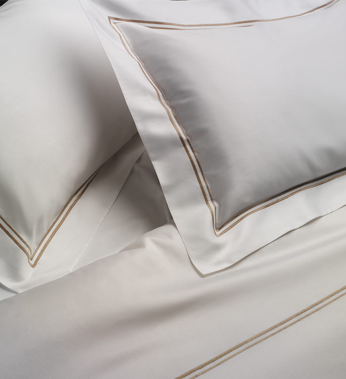 crisp oxford bordered pillows and bed linen with two embroidered lines