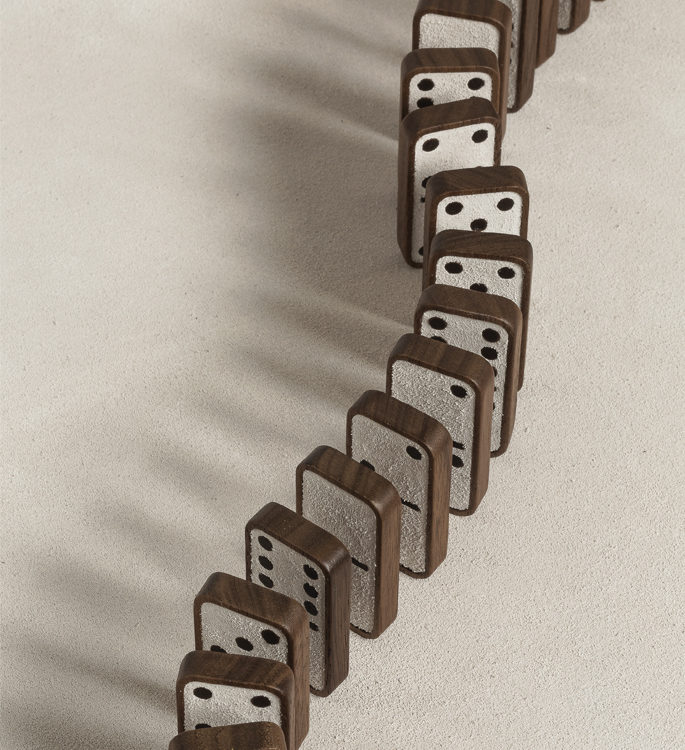 dark wooden dominoes with suede faces, lined up ready to fall