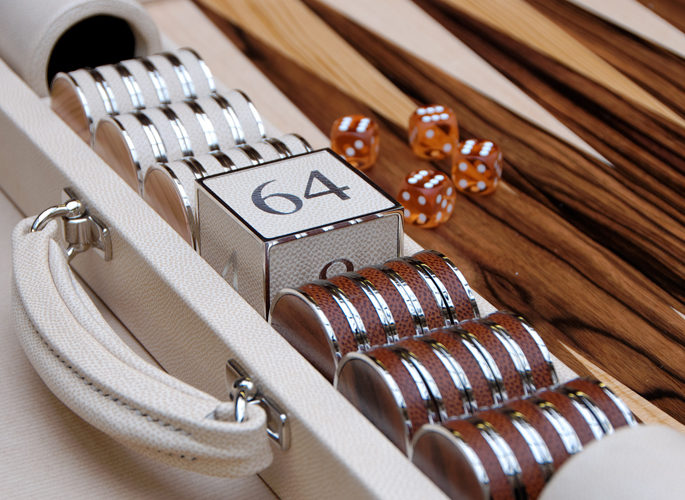 a leather and wooden backgammon set with sterling silver games pieces and a large dice