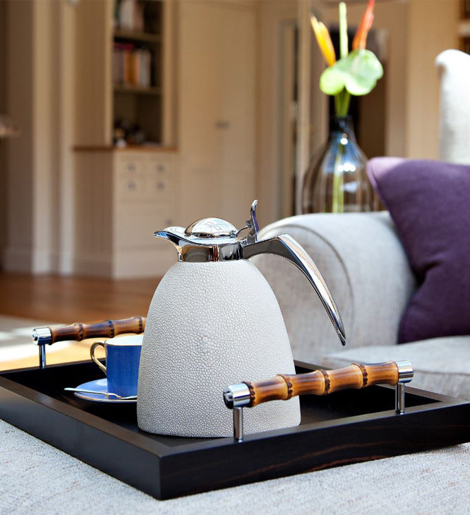 a dark wooden tray with a white leather water jug and a bright blue tea cup on top