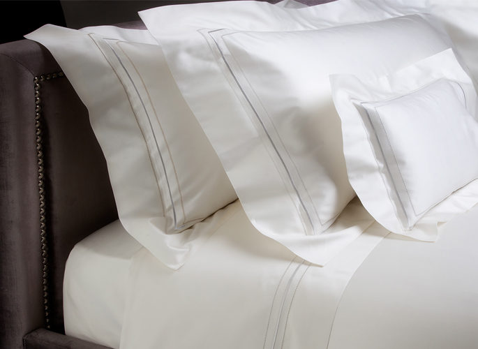 white bed linen with two embroidered lines and three pillows